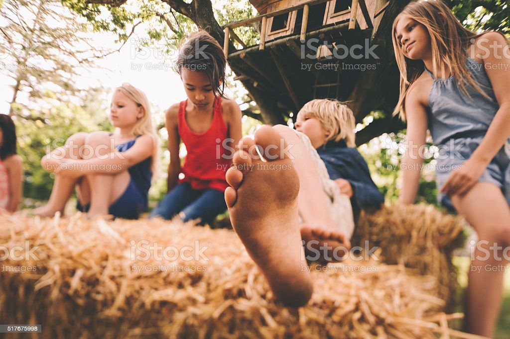 Children lying on hay bales under a wooden treehouse stock photo