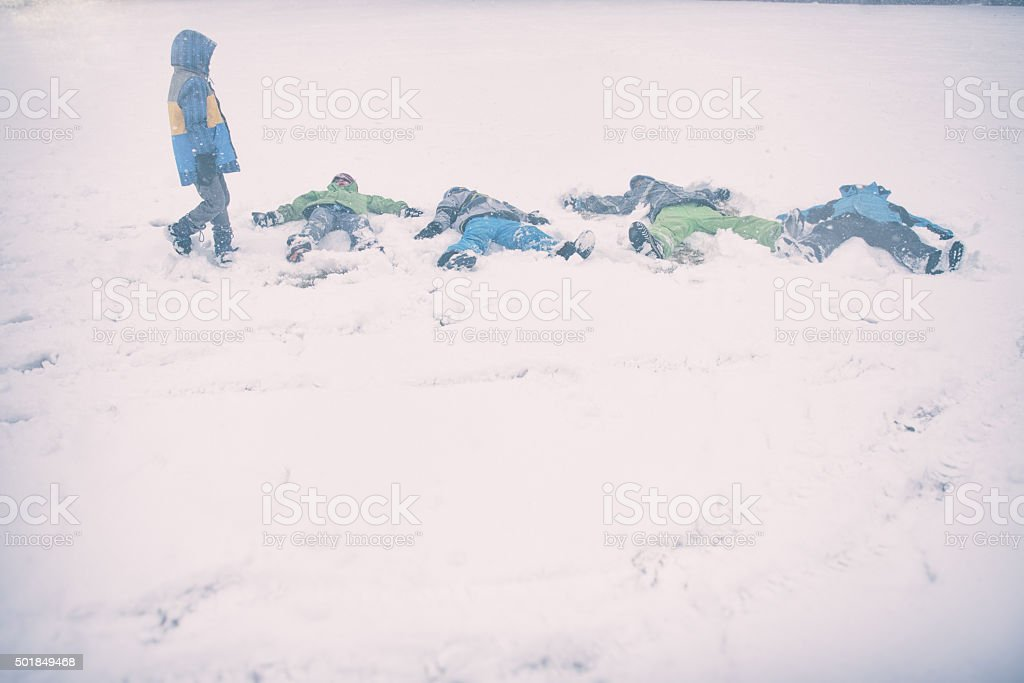 Children make snow angles on a storm day stock photo