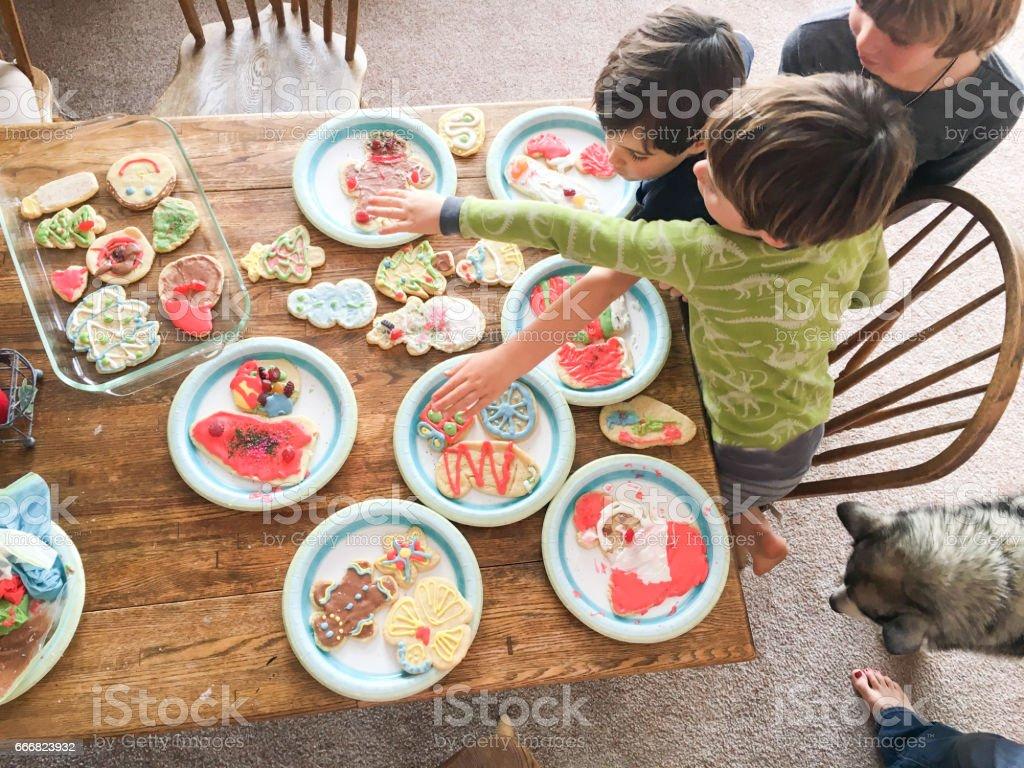 children making and sharing sugar cookies stock photo
