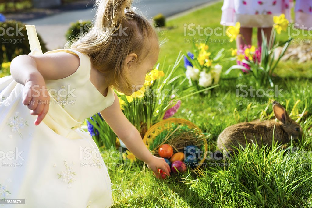 Children on an Easter egg hunt with flowers and a rabbit stock photo