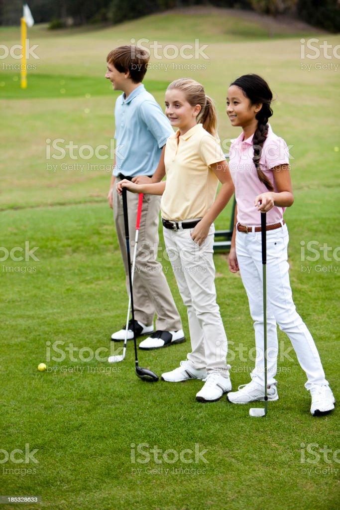Children on golf driving range stock photo