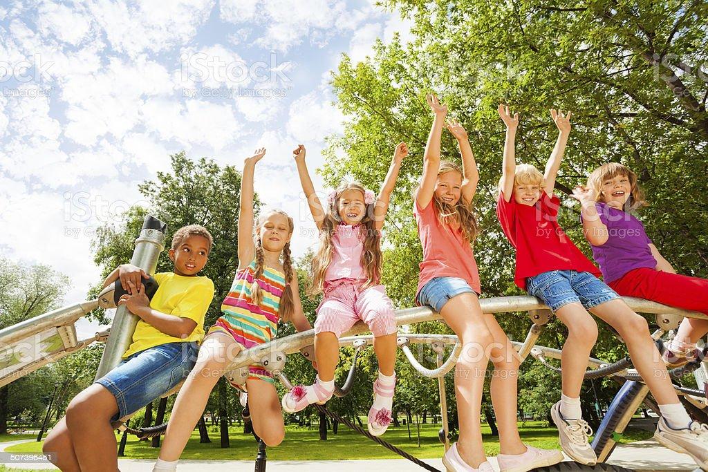 Children on round bar of playground construction stock photo