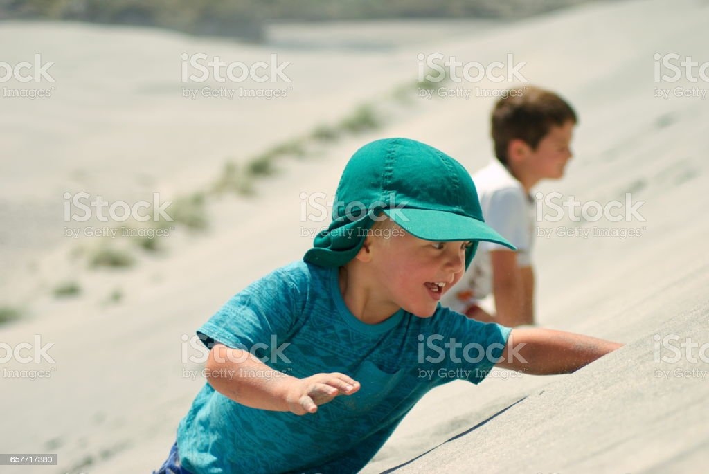 Children on Sand Dunes on the Beach stock photo