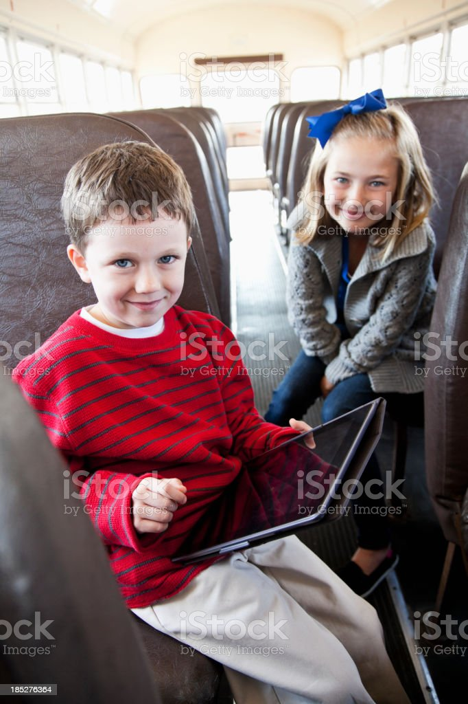 Children on school bus playing with digital tablet royalty-free stock photo