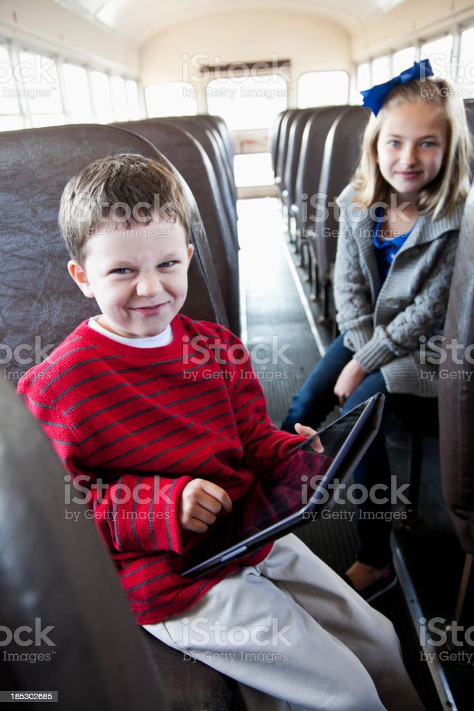 Children on school bus playing with digital tablet stock photo