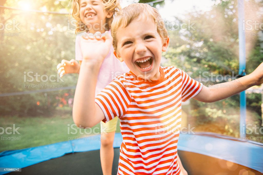 Children on Summer Holidays Jumping on Trampoline stock photo