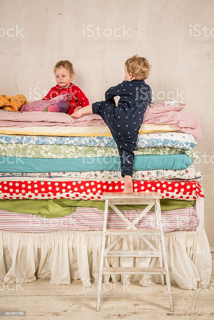 Children on the bed - Princess and the Pea. stock photo