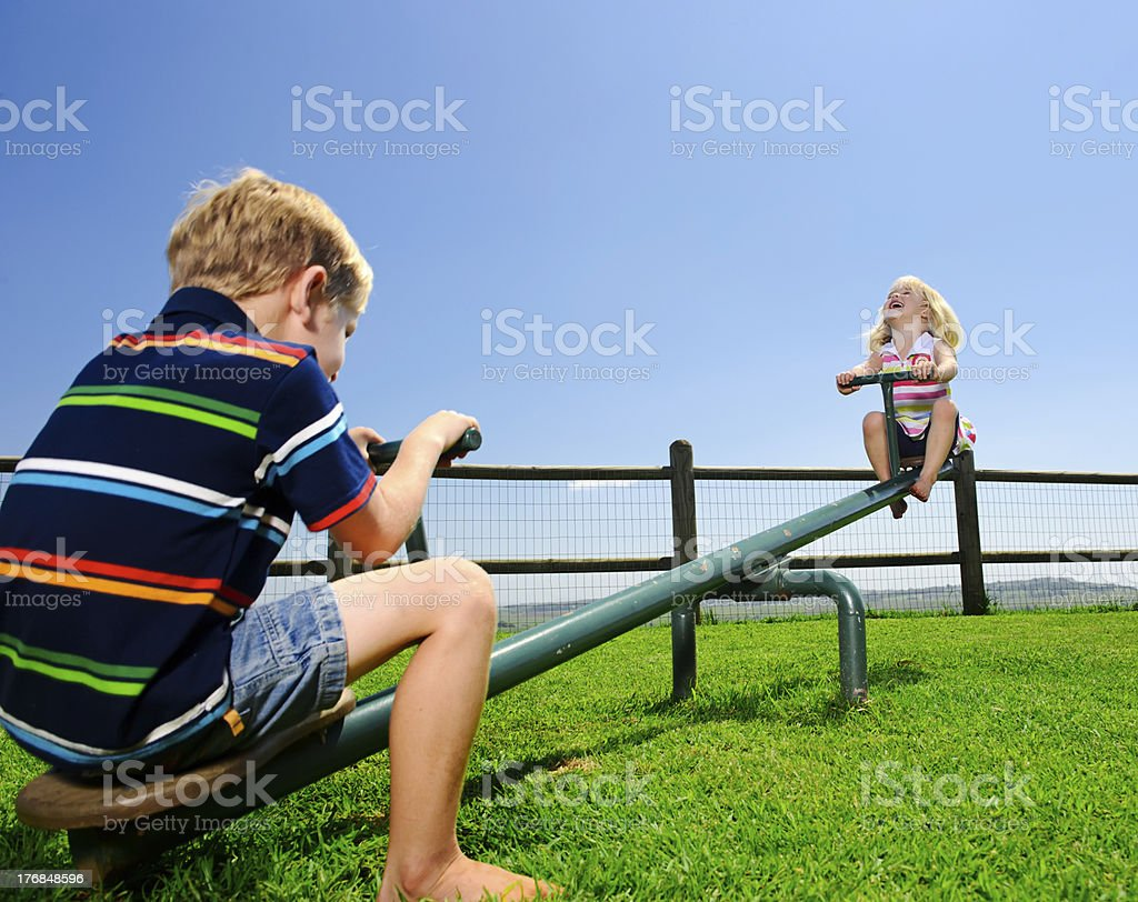 Children on the seesaw in a playground stock photo