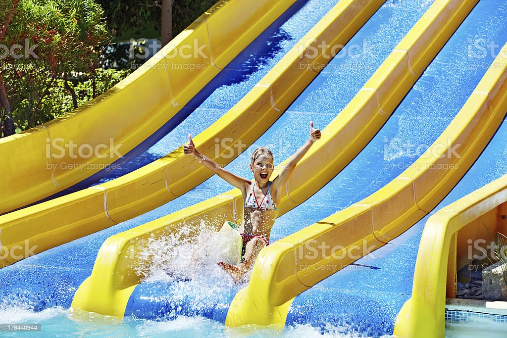 Children on water slide at aquapark. stock photo