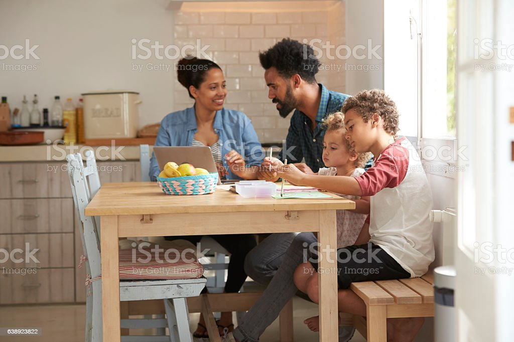 Children Paint At Kitchen Table As Parents Look At Laptop stock photo