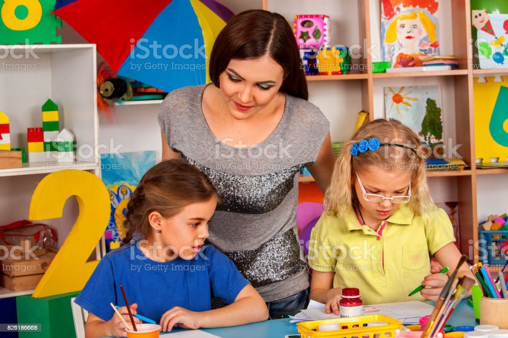 Children painting and drawing together. Craft lesson in primary school. stock photo
