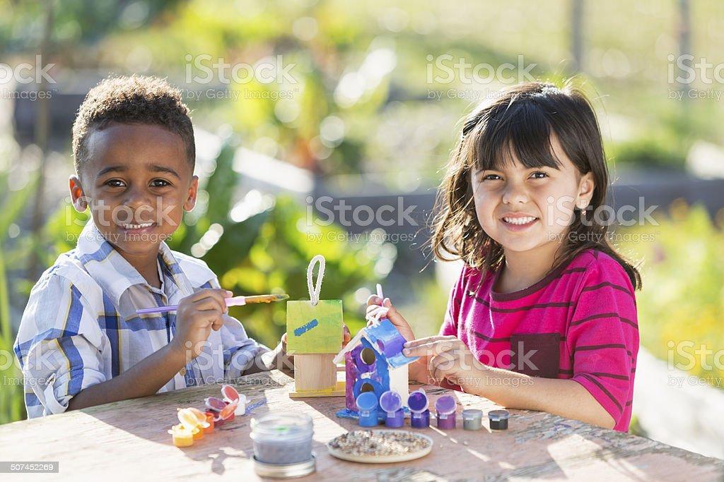 Children painting bird houses stock photo