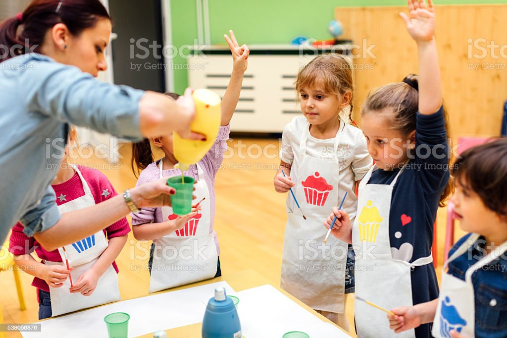 Children Painting Their Hands With Watercolors stock photo