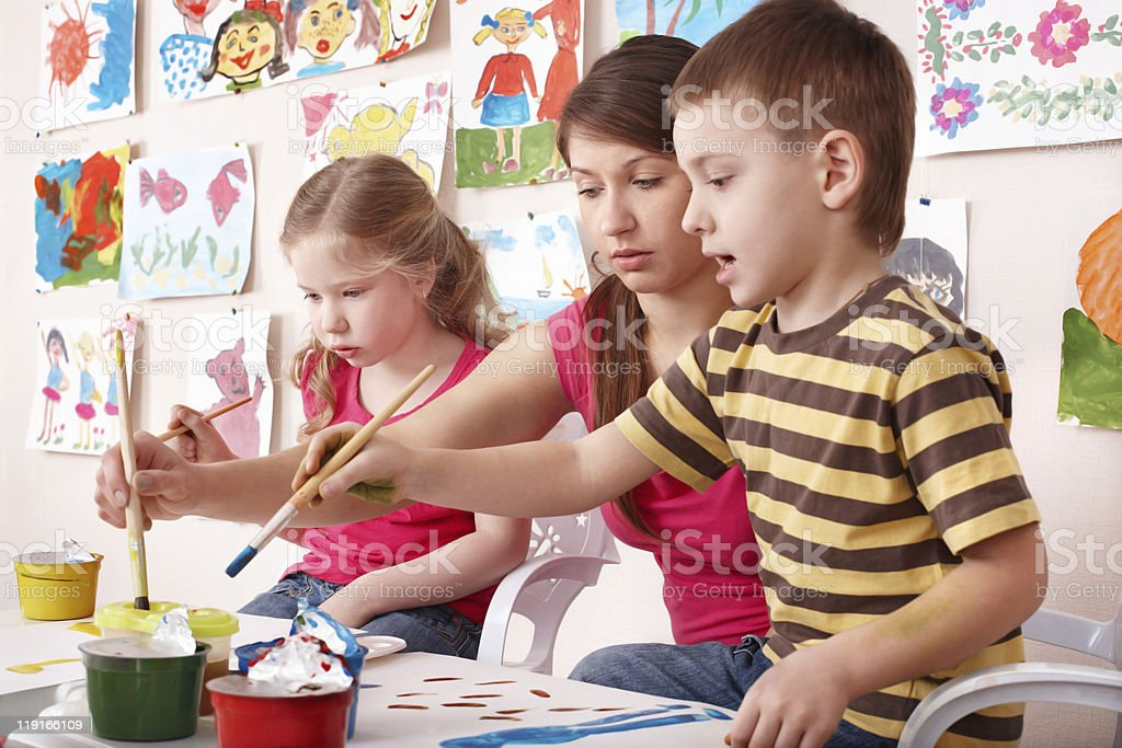 Children painting with teacher in art class. royalty-free stock photo