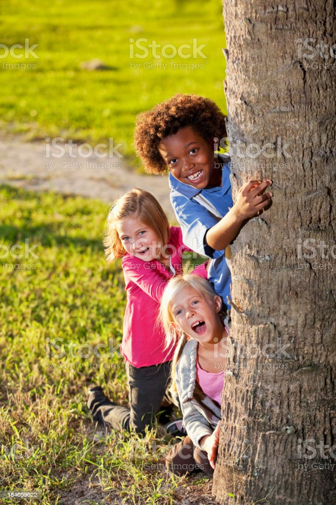 Children peeking out from behind a tree royalty-free stock photo