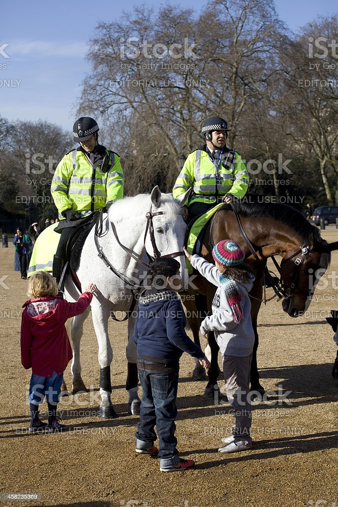 Children pet two mounted police horses stock photo