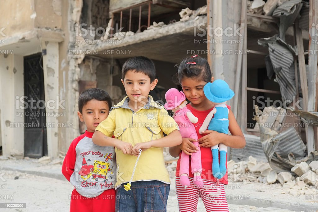 Children play among the destroyed houses stock photo