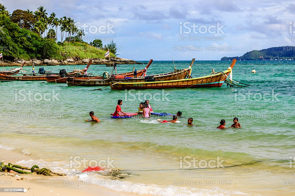 Children play in sea near boats, Phuket, Thailand stock photo
