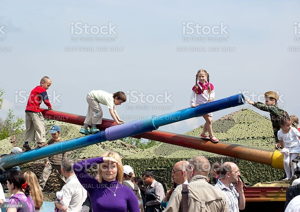 Children play on tank barrels during Victory Day celebration stock photo