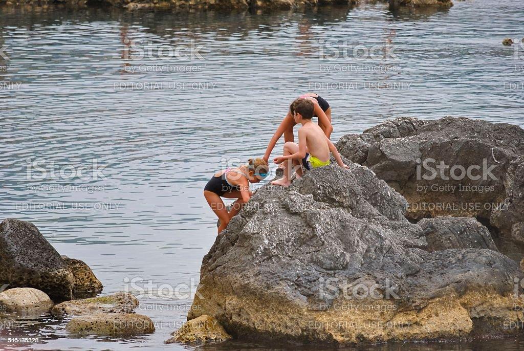 Children play on the big stones stock photo