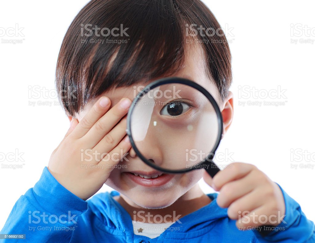 Children play with a magnifying glass stock photo