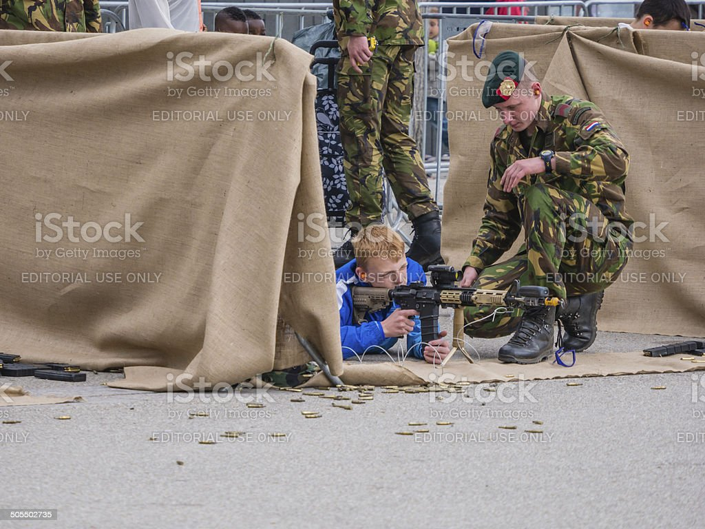 Children play with weapons on Army Day stock photo