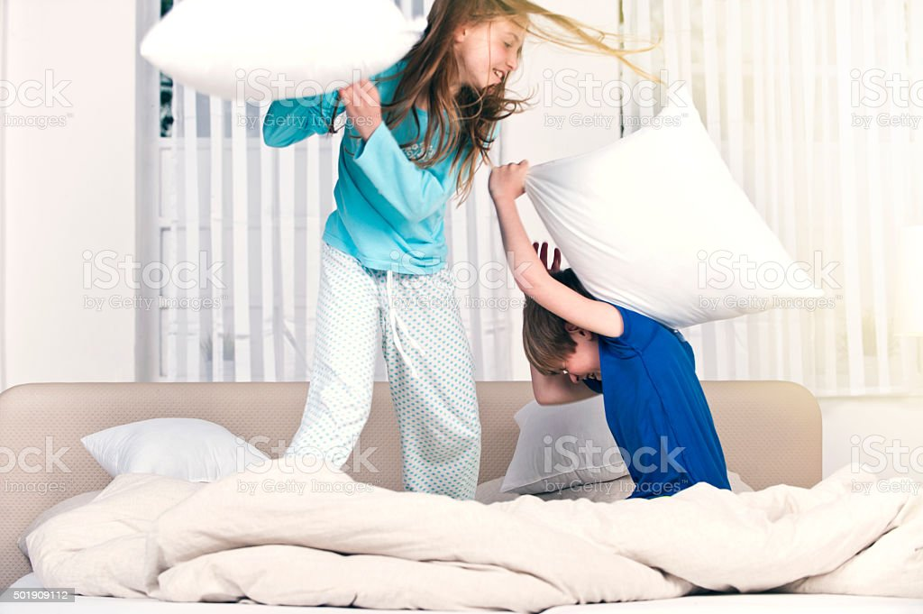 Children playfighting on parents' bed stock photo