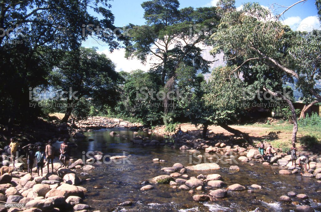 Children playing along river emanating from Mulanje Massif in southern Malawi Africa stock photo