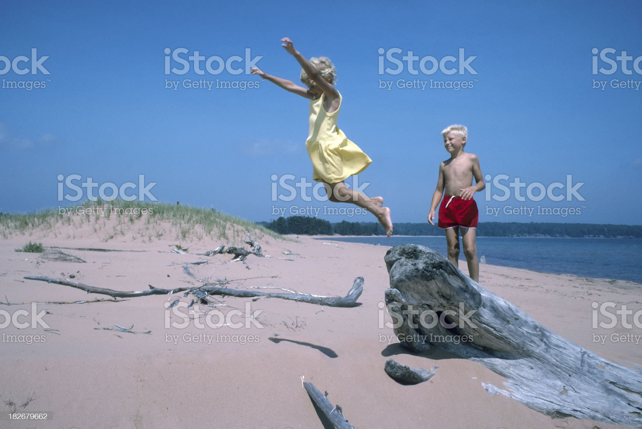 children playing and jumping on a sandy beach royalty-free stock photo