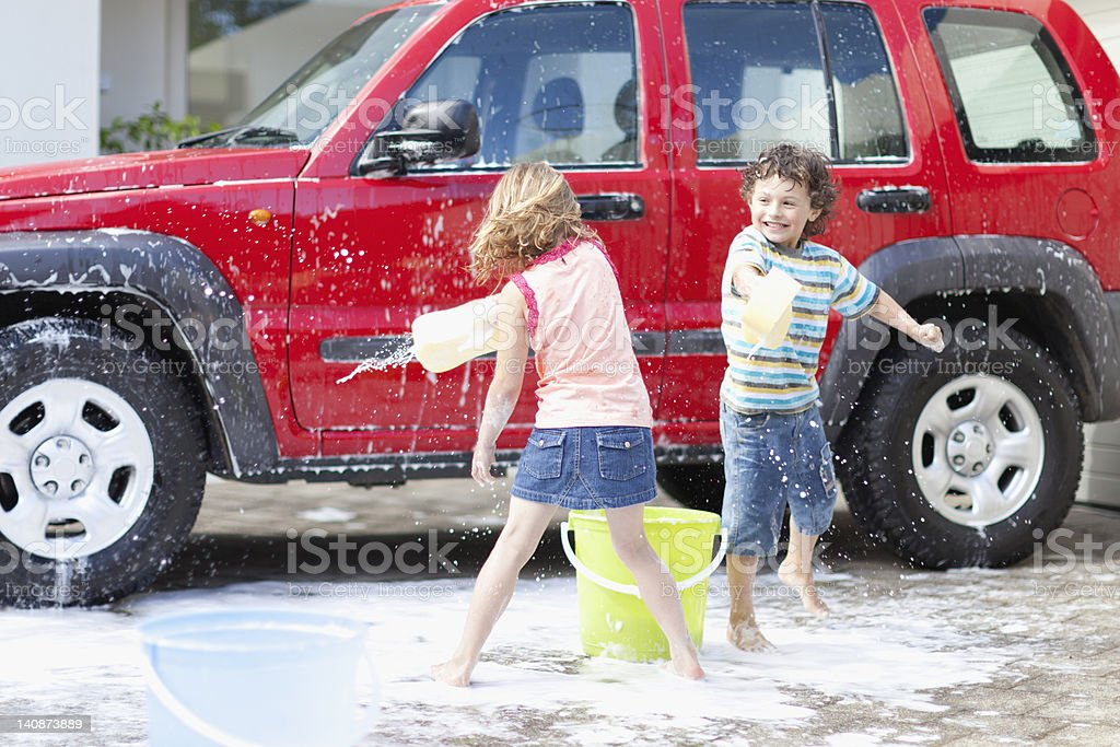 Children playing and washing car stock photo
