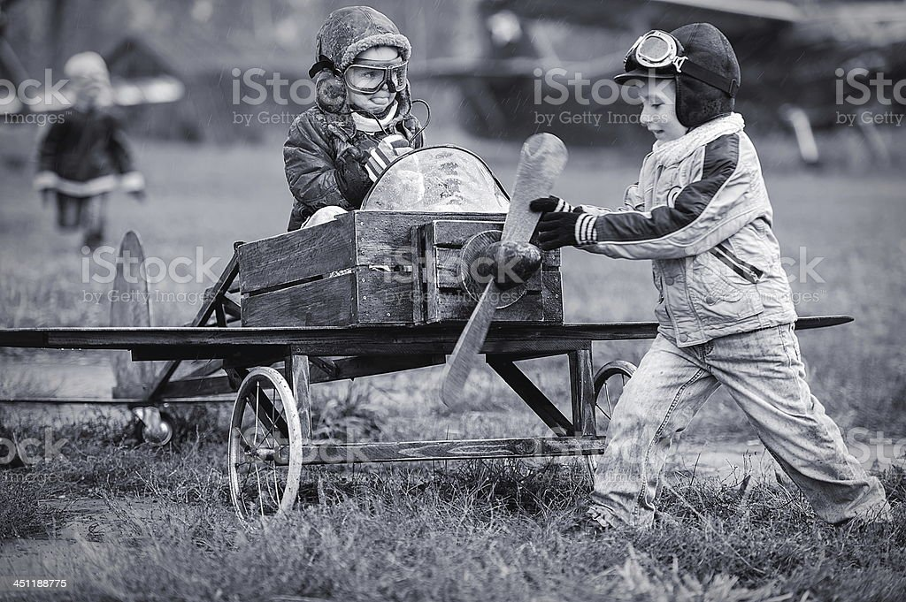 Children playing as pilots with homemade airplane stock photo