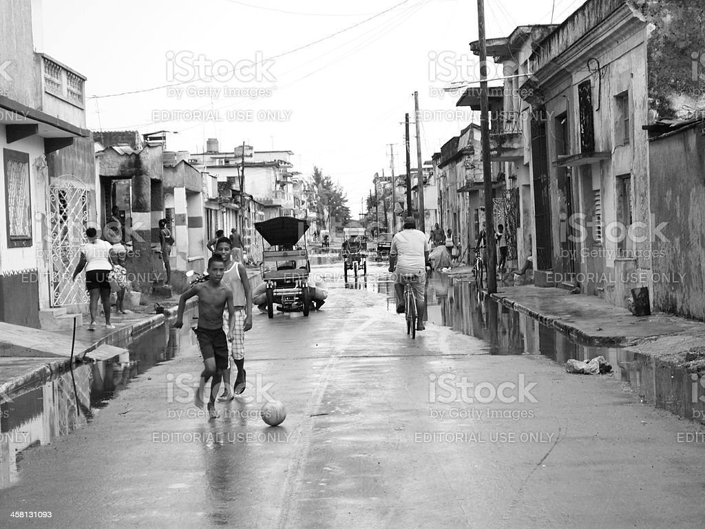 Children playing ball, bici-taxis and bike riders in Caredenas, Cuba royalty-free stock photo