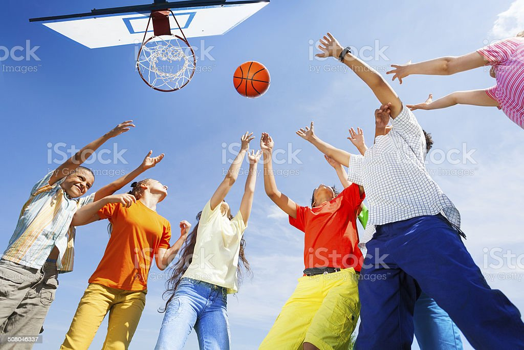 Children playing basketball with a ball up in sky stock photo