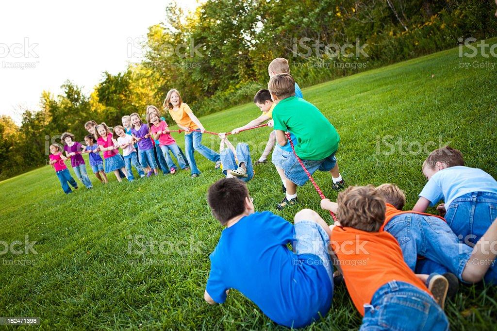 Children Playing Girls Versus Boys Tug-of-War Game Outside royalty-free stock photo