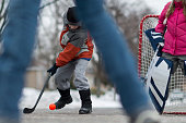 Children Playing Hockey with a Ball and Hockey Sticks