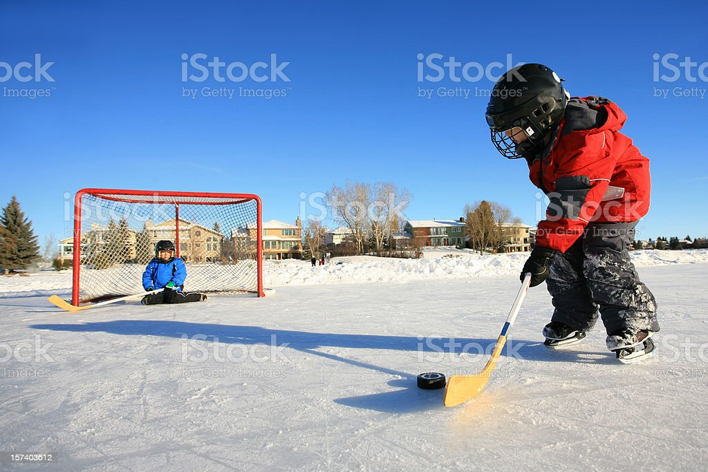 Children Playing Ice Hockey on Outdoor Pond or Rink stock photo