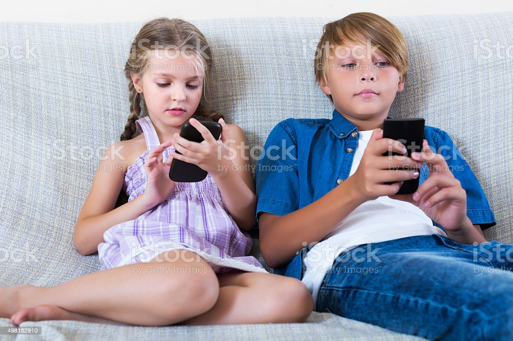 Children playing in mobile phones stock photo