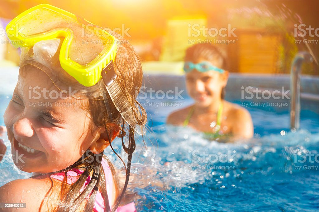 Children playing in pool. Two little girls having fun stock photo