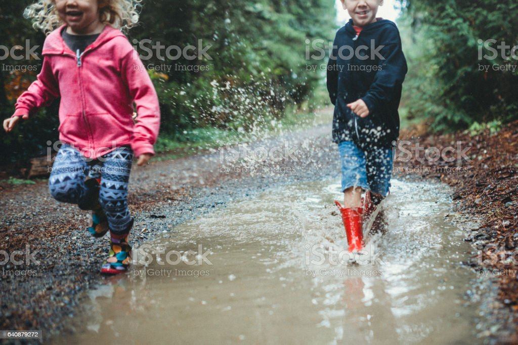 Children Playing in Rain Puddle stock photo