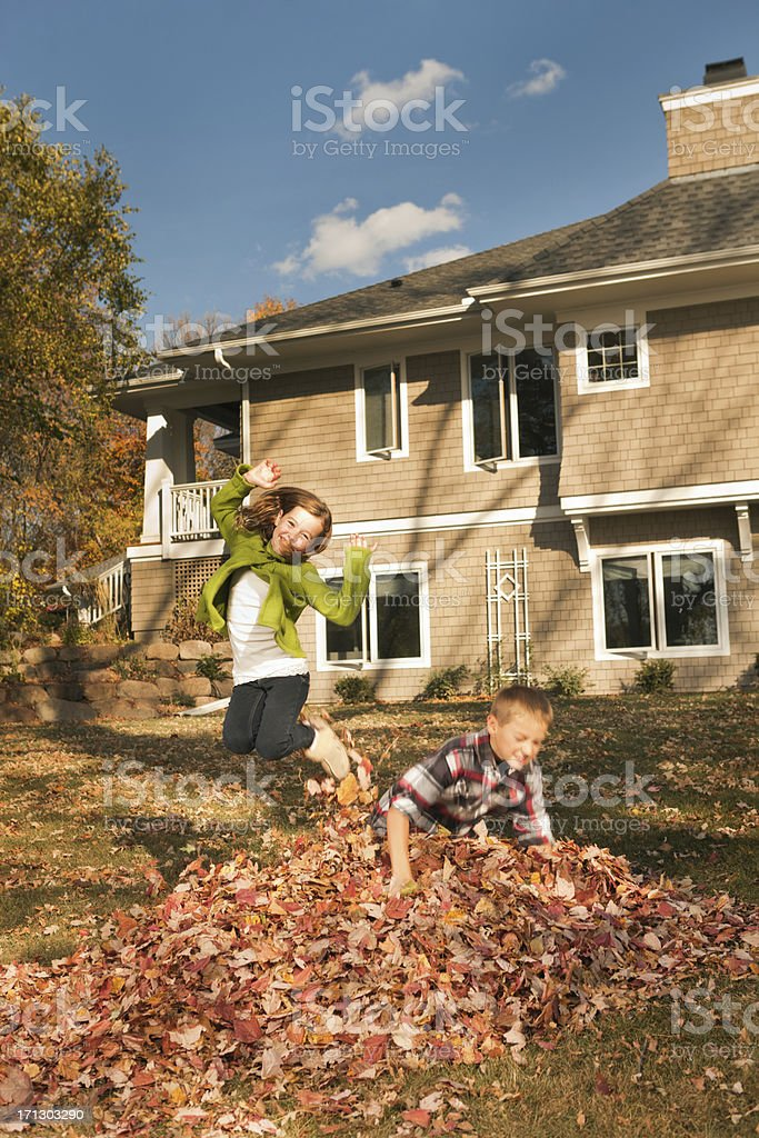 Children Playing in the Fall Leaves Pile by Their Home royalty-free stock photo