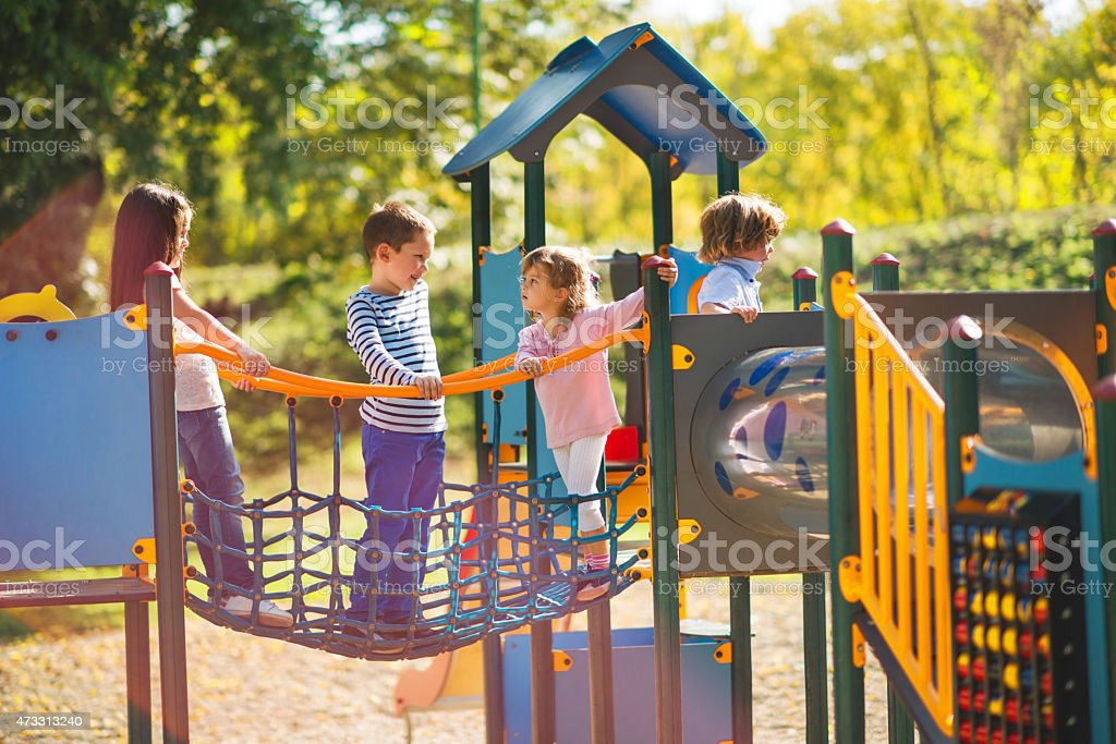 Children playing in the park at playground and communicating. stock photo