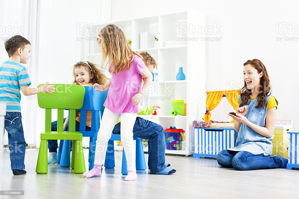 Children Playing Musical Chairs Indoors. stock photo