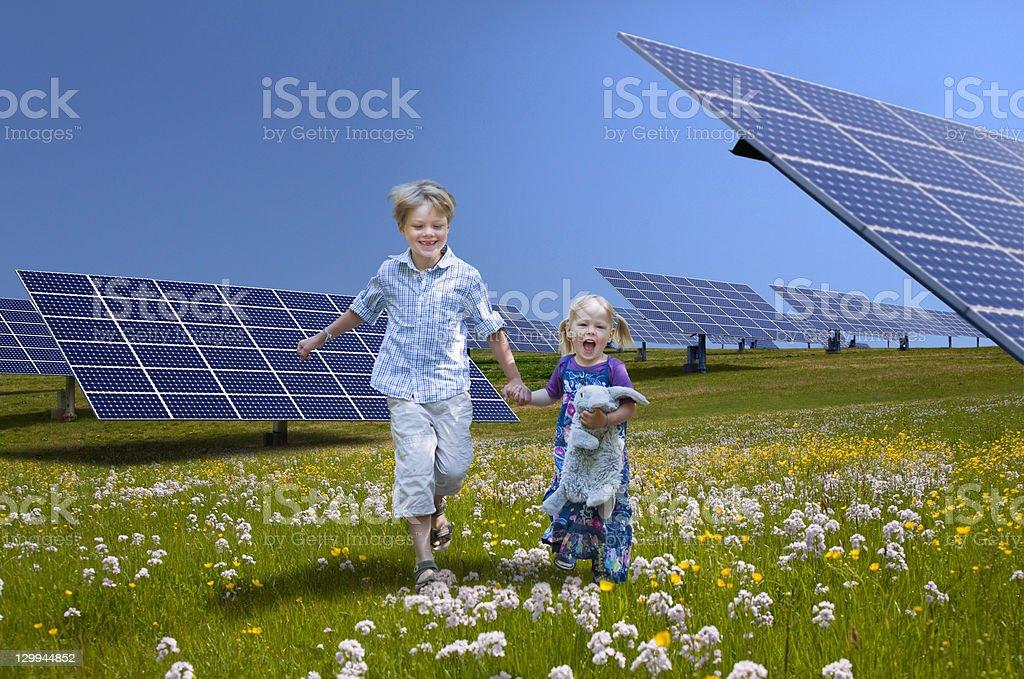 Children playing near solar panels stock photo