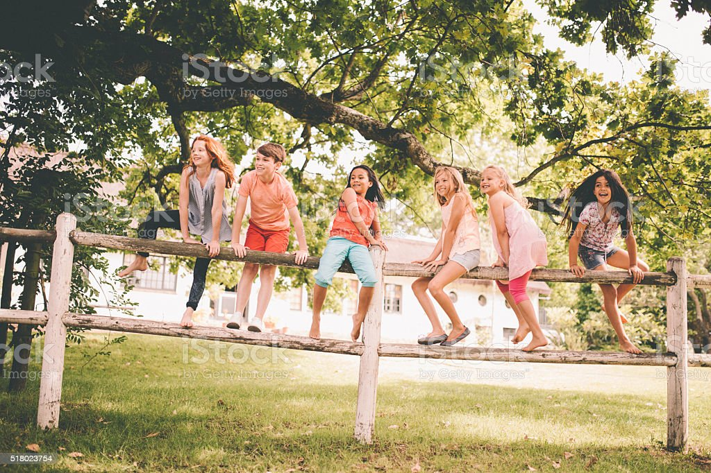 Children playing on a rustic wooden fence in a park stock photo