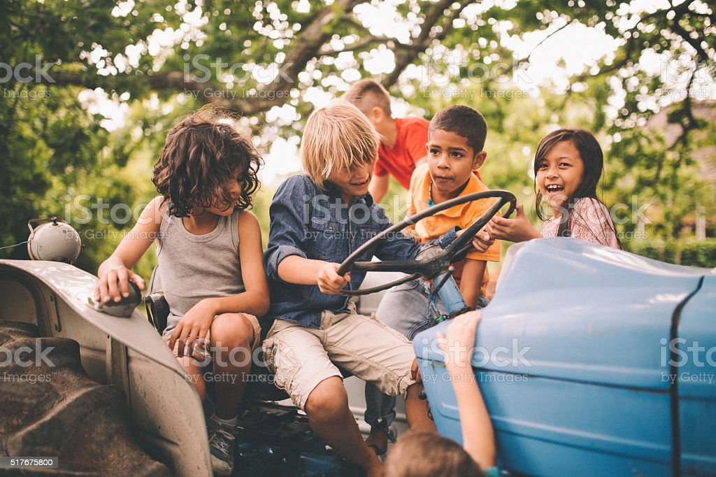 Children playing on a tractor on a summer day stock photo