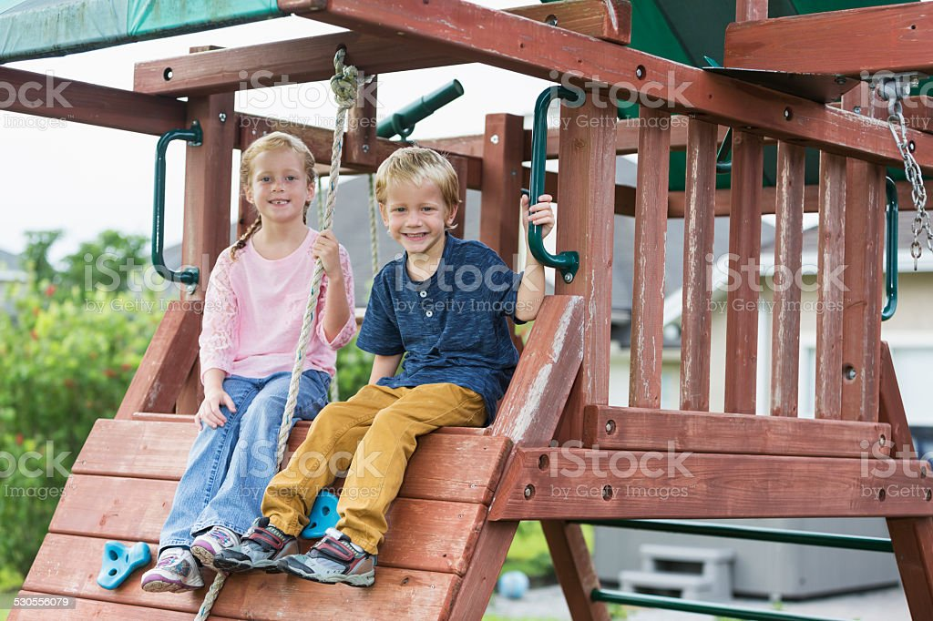 Children playing on backyard playset stock photo