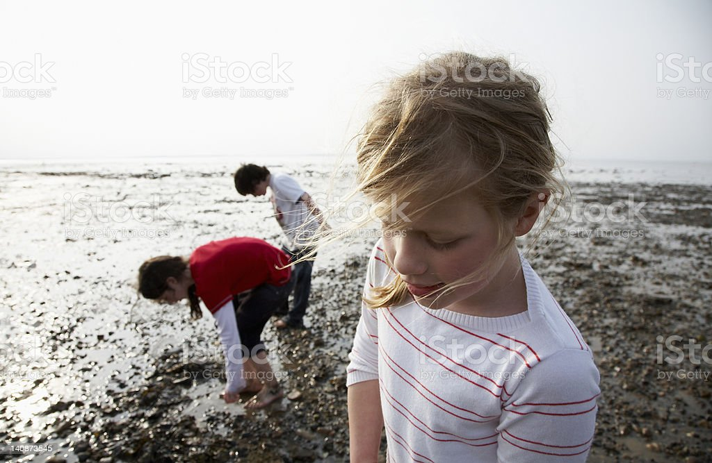 Children playing on rocky beach stock photo