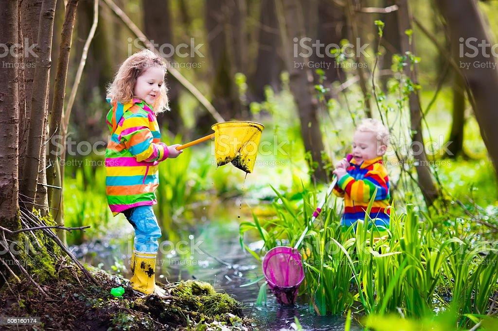 Children playing outdoors catching frog stock photo