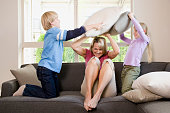 Children playing pillow fight with mother at home