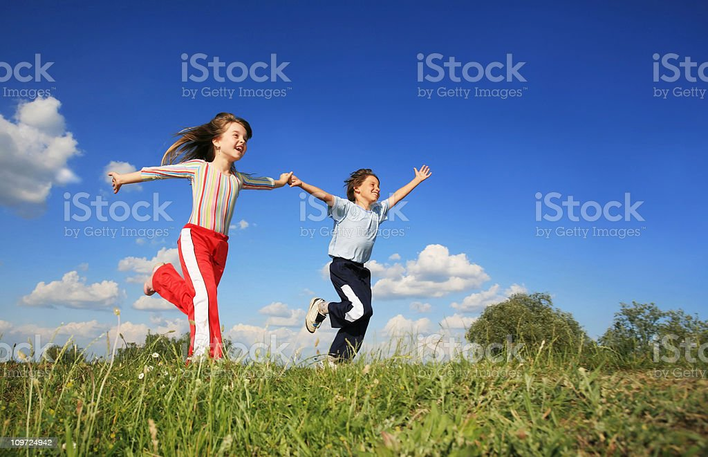 Children playing running on meadow stock photo